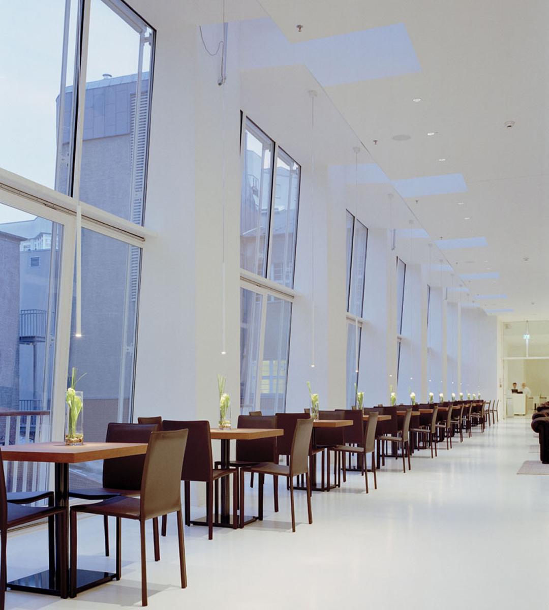 Hell-Dunkel-Kontrast: Holztische im strahlend weißen Frühstücksraum mit hoher Decke und Lichtvouten. Ein lebendiger Kommunikationsraum für alle Hotelgäste.