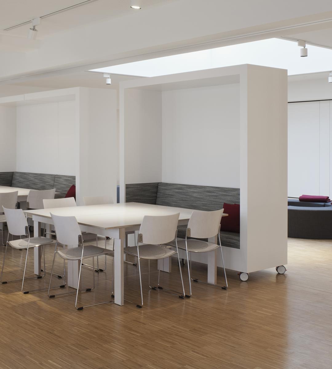 Systelios Privatklinik, Speisesaal mit quadratischen Tischen aus Multiplex mit weißtransparenter Beschichtung, Boden aus robustem Eichen-Lamellenparkett. Leichte Stapelstühle von Brunner mit losen Filzauflagen. Hohe weiße Sitznischen auf Rollen grenzen als Raumteiler die Sitzgruppen zur dahinter liegenden Aktionsfläche ab. Mit ihnen lassen sich spontan neue Räume bilden. Deckenstrahler spenden fokussiertes Licht auf den Tischen. Bild: Werner Huthmacher