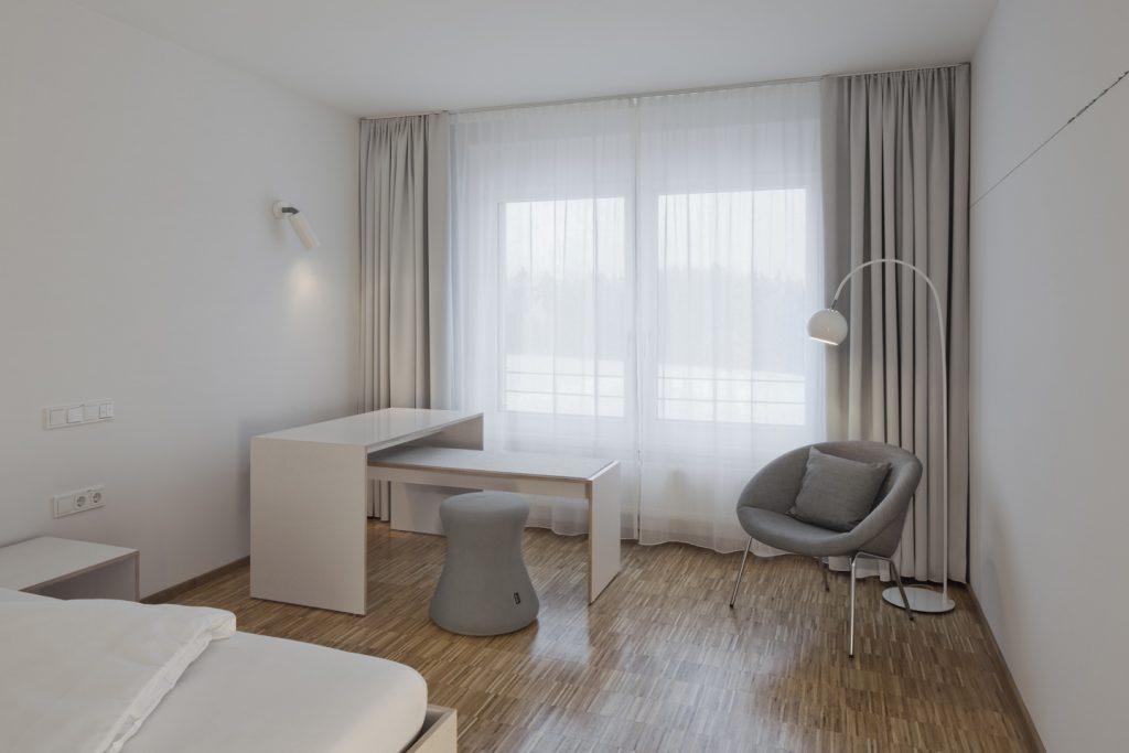 Systelios Privatklinik, helles Klient*innenzimmer mit leichten modularen Möbeln auf Eichenparkettboden. Bett mit Stauraumschublade, Bank, Tisch und Rahmenhocker aus Multiplex mit weißtransparenter Beschichtung, weißer Wandstrahler und mobile Kugelstehleuchte für richtbares Licht, leichter Polstersessel von Walter Knoll mit losem Kissen. Farbige Zusatzausstattungen wählen die Klient*innen in Aussuchräumen. Reuter Schoger Architektur Innenarchitektur Berlin, Bild: Werner Huthmacher