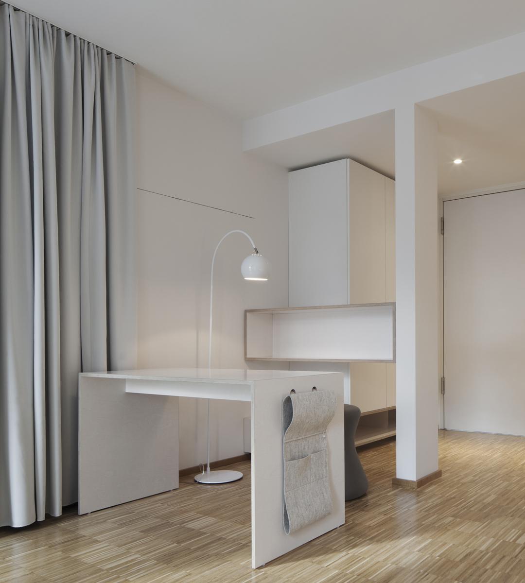 helles Klientenzimmer mit Eichenparkettboden und weiß lasierten Holzmöbeln. Schreibtisch mit Untensilientasche aus hellgrauem Filz, in Wand bündig eingeputzte Magnetleiste, steingrauer Ergohocker, weiße Kugelstehleuchte