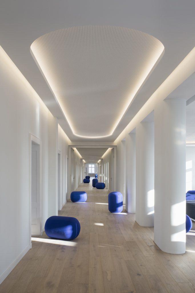 Der 125 Meter lange Korridor als Raumerlebnis mit blauen Kapselsitzen und leichten Stehtischen für informelle Konversation.