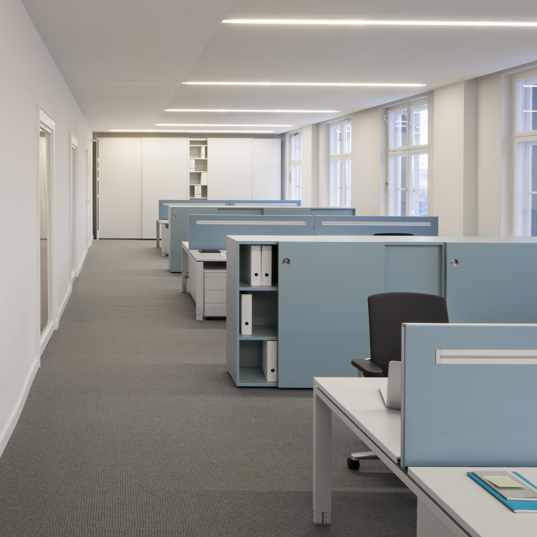 Halbhohe hellblaue Stauraummöbel gliedern und strukturieren anstelle von Trennwänden die Gruppenbüros.