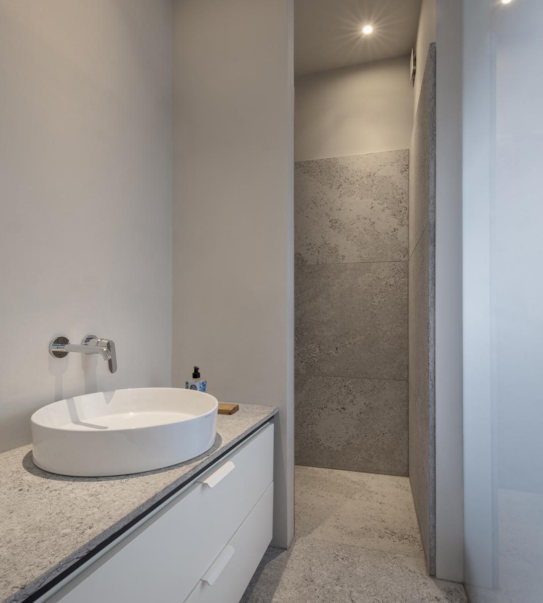 Durch die Verwendung von großformatigen Natursteinplatten mit gekordelter Oberfläche in der Badgestaltung entsteht ein intensiver und elegant wirkender Raum