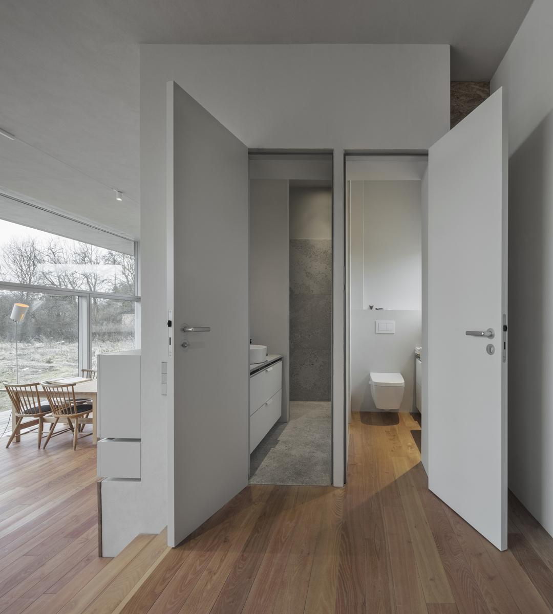 Hier zählt jeder Zentimeter: Zwei platzsparende Sanitärräume mit Tageslicht, das WC an der Außenwand, das flächeneffiziente Duschbad innen, getrennt vom WC durch eine transluzente blickdichte Glaswand