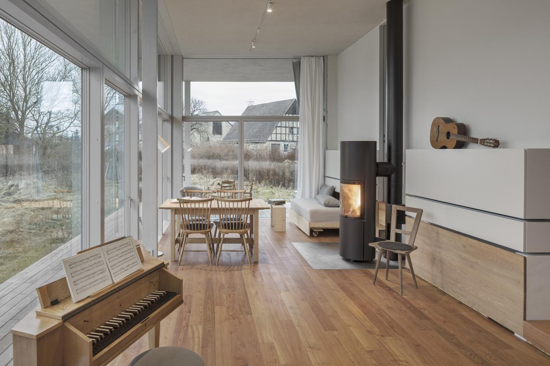 Der gemütliche Wohnbereich mit Spinett, schwarzen Holzkaminofen und mobilem Tagesbett, das nach Bedarf durch Herausziehen vergrößert werden kann.