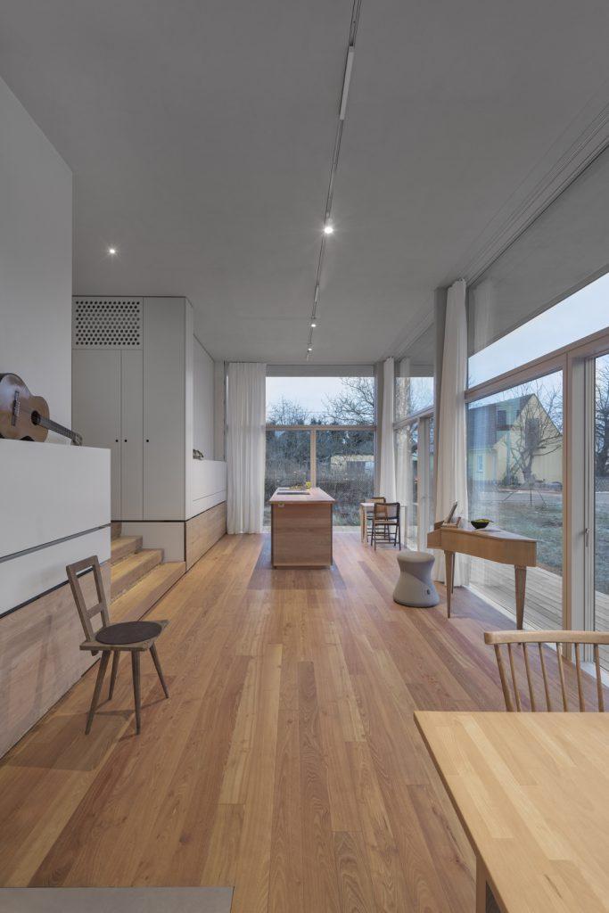 Der lange hohe Wohnraum reicht von einem Ende des Hauses zum anderen mit den Holzdielen aus widerstandsfähiger roter Robinie, aus denen ebenso die Terrassen als auch der Küchenblock mit Küchenarbeitsplatte und die Vorrats- und Stauraumschubladen sind.