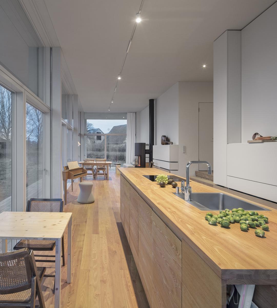 Der Blick durch die Westfassade aus Glas fällt auf die umliegenden großen Scheunen des Dorfes. Der schwarze, moderne Holzkaminofen an der rechten Wand genügt zur Beheizung des Hauses.