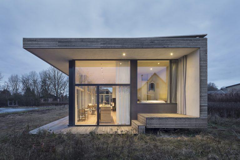 Minimalistische moderne Fassade eines Holzhauses zum Wohnen auf kleiner Grundfläche. Die Hauptmaterialen der Fassaden sind Holz und Glas.