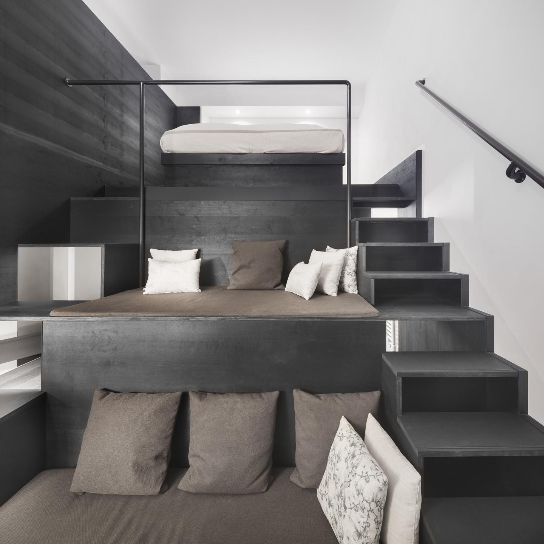 hohes Hotelzimmer mit Stufen und Podesten aus dunkel lasiertem Holz