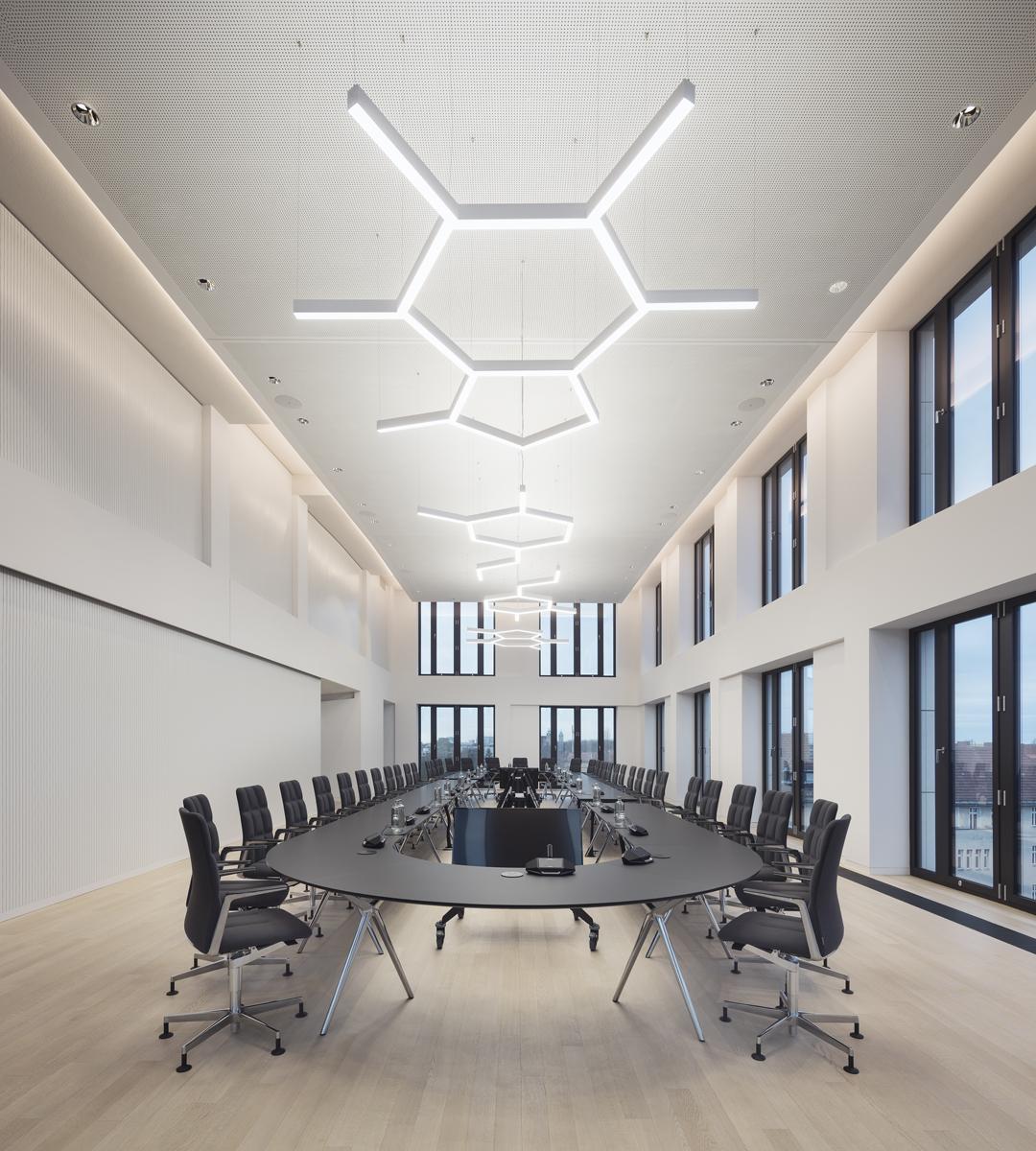 Konferenztisch aus 20 flexiblen Modulen in langer Ovalform für 42 Drehsessel in zweigeschossigem Raum mit großen Fenstern. Neutralweißes Licht aus vier dimmbaren LED-Pendelleuchten in den Molekülformen Coffein, Theobromin, Dopamin.