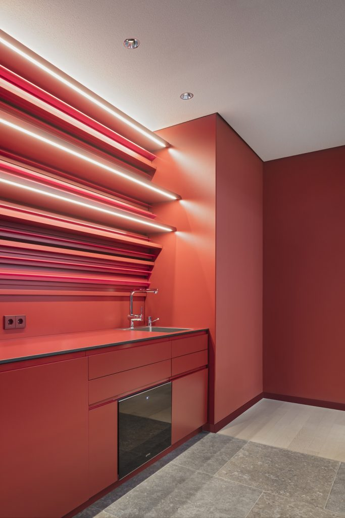 Das Farbkonzept der Raumecke für die Espresso-Bar greift die tiefrote Farbe des Apotheken-Logos auf. Das Wandrelief aus rot lackiertem Holz und fluoreszierendem Acrylglas dient als Regal.