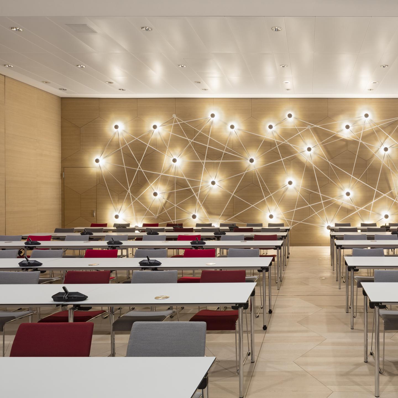 Der Plenarsaal ist mit mobilen Trennwänden in drei Konferenzbereiche teilbar. Klapptische und Stapelstühle bieten Flexibilität. Hexagonales Tafelparkett und Akustikpaneele sind aus Eiche. Die Wandgestaltung aus Stabwerk und Licht symbolisiert die Vernetzung der Apothekerverbände der Bundesländer.