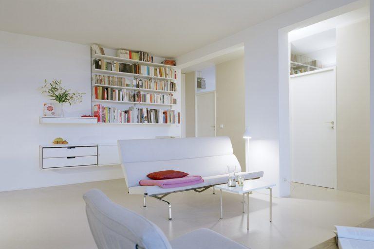 Helles weißes Wohnzimmer mit modernem Sofa von Ray und Charles Eames. Das Regalsystem von Dieter Rams passt als Aufbewahrungslösung perfekt zur luftigen Atmosphäre des Allraums von Alvar Aalto.