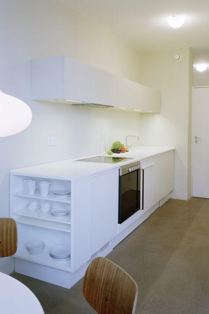 Monolithische Einbauküche aus weißem Mineralwerkstoff. Das offene Regal auf der Stirnseite der Unterschrankzeile ist sowohl praktisch und gestalterischer Abschluss des Küchenblocks.