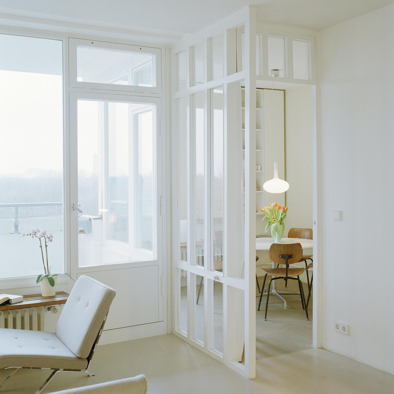 Ein einfacher, aber eleganter Raumteiler aus Glas sorgt für Transparenz und fließende Übergänge zwischen den Räumen und integriert den Aufenthalt in der Küche in die multifunktionale Nutzung im zentralen Allraum.