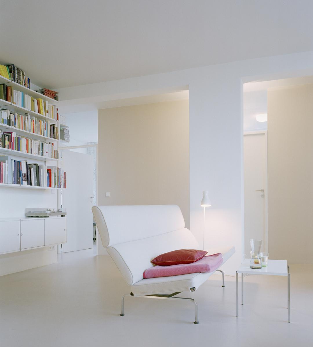 Farbakzente wie das Rosa der Überwurfdecke und das Rot der Kissen kommen im hellen weißen Wohnzimmer intensiv zum Ausdruck.