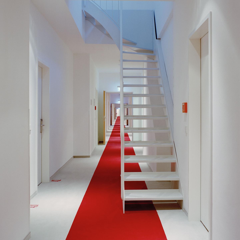 Ein Blick in die Unendlichkeit: die nicht enden wollenden roten Läufer in den Korridoren der Hotelzimmer, mit der subtilen Einbettung der Zimmernummern in den Bodenbelag.