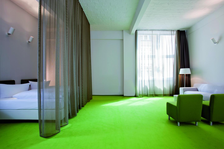 Sattes leuchtendes Grün als Hauptgestaltungsmittel für ein lebhaftes Hotelzimmer mit Loftcharakter, das in der Nutzung Spaß macht.