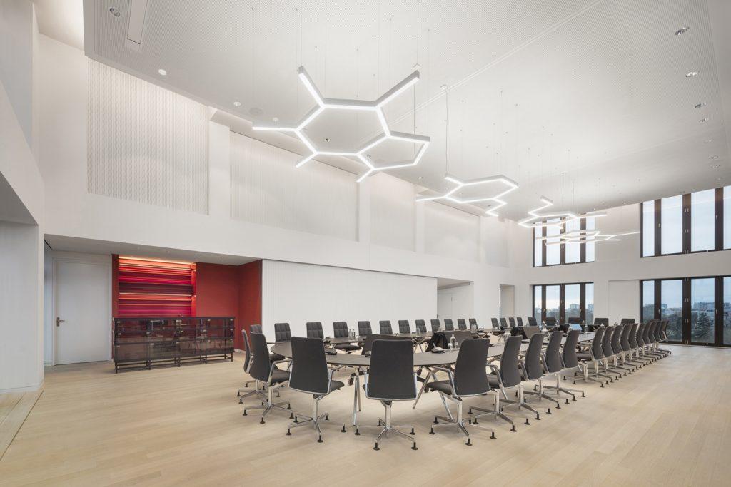 Modularer ovaler Konferenztisch und 42 Konferenzsessel in zweigeschossigem Konferenzraum mit bodentiefen Fenstern. Braune Espresso- Glasbar in roter Nische mit fluoreszierenden Regalkanten.