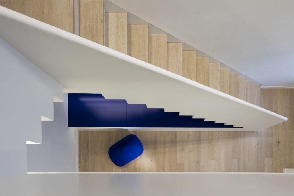 Die interne offene Treppe verbindet die Gemeinschaftsräume Cafeteria und Bibliothek. Das stärkt die Zusammengehörigkeit der Mitarbeiter*innen aus den verschiedenen Bürogeschossen.