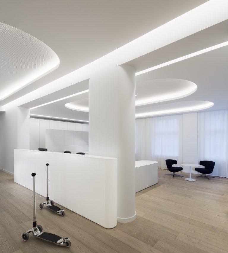 Ein Blick auf die moderne weiße Rezeption mit indirektem Licht aus den Vouten der abgehängten Akustikdecke.