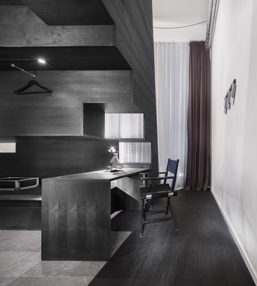 Blick von Hotelzimmertür Richtung Fenster zeigt die Nutzung unter dem multifunktionalen Treppenelement. Bild: Werner Huthmacher